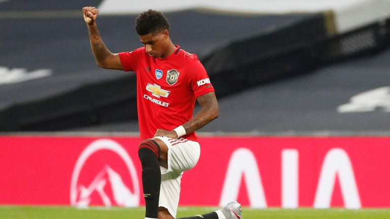 Manchester United's Marcus Rashford raises his fist as he kneels in support of the Black Lives Matter campaign