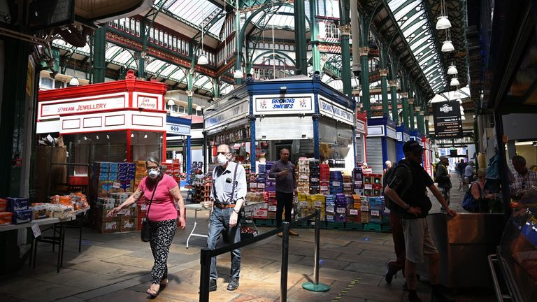 Customers, many wearing protective face masks, shop for goods as more stalls open for business in the indoor Kirkgate market in Leeds, northern England following the easing of the lockdown restrictions during the novel coronavirus pandemic on June 1, 2020