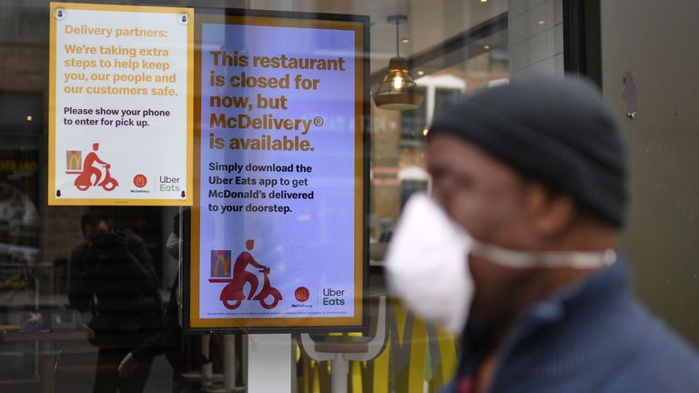A mask-wearing member of the public walks past a closed McDonald's