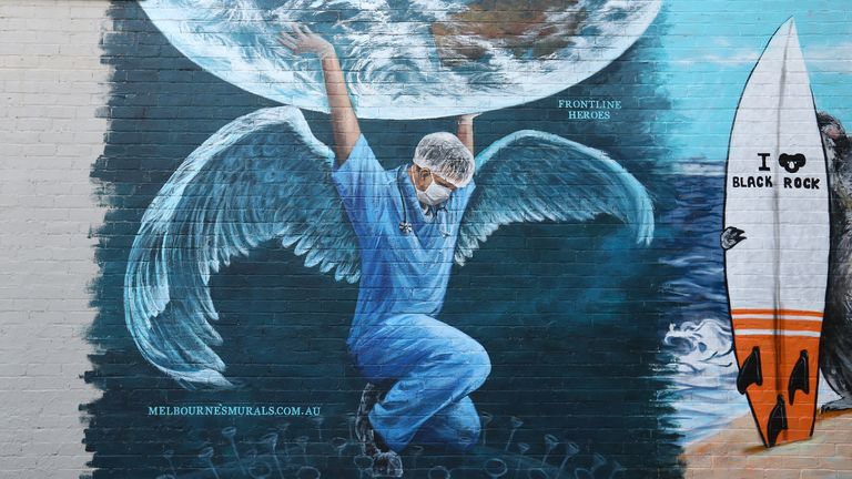 A mural honours medics in Melbourne, Australia, which will see restrictions reimposed on Monday