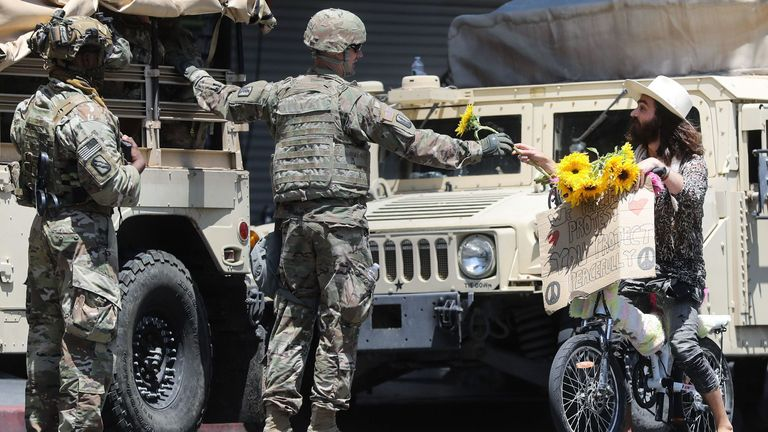 A protester hands a flower to a National Guard soldier during a peaceful demonstration over George Floyd's death in Hollywood