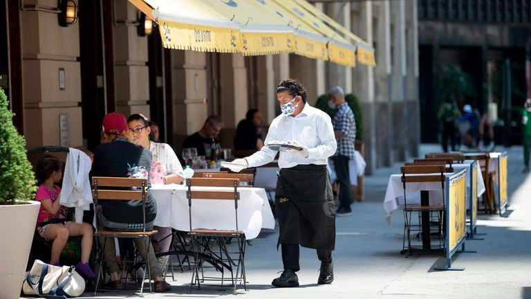 A waiter serves customers in New York City