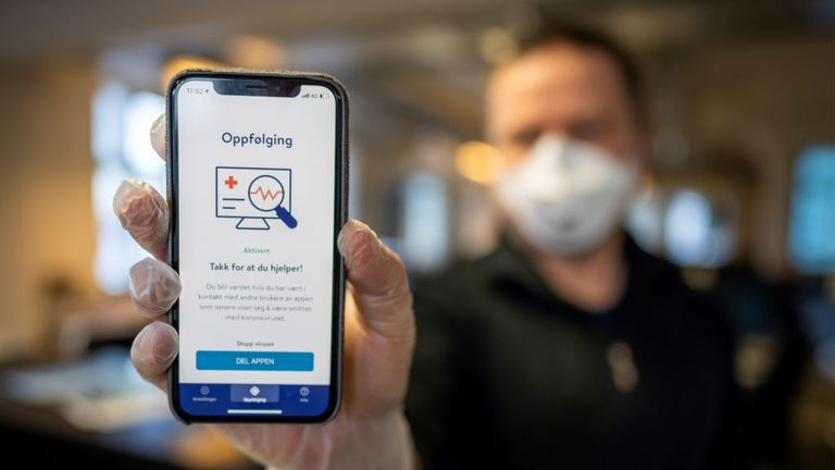A man holds a smartphone showing a tracking and tracing app launched by the National Institute of Public Health to try to halt a return of the new coronavirus, on April 17, 2020 in Oslo. - Norway, one of the first European countries to begin lifting confinement measures, is launching a smartphone tracking and tracing app that has been developed to provide health authorities a better picture of the spread of COVID-19 and tell users if they have been in contact with the disease. (Photo by Heiko Ju