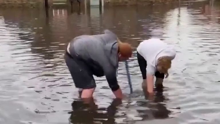 Two people try to reach drain in flooded Nottingham street