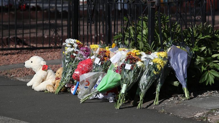 Flowers have been left near the flat where a fire caused the death of three young children