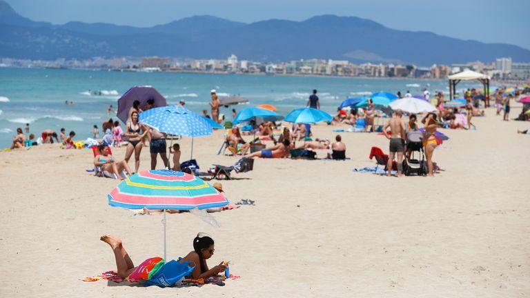People sunbathe at Playa De Palma beach, as Spain prepares to officially reopen its borders