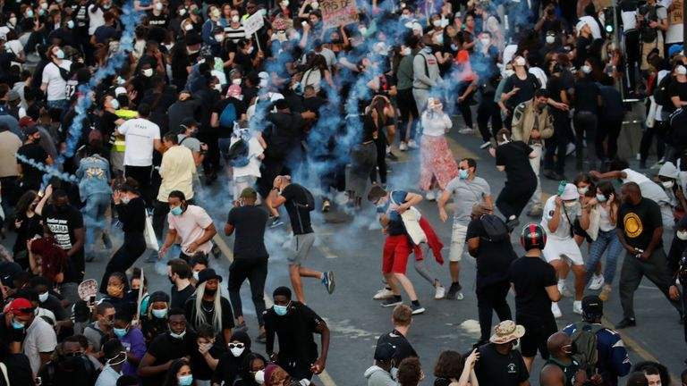 People run from tear gas as they attend a banned demonstration planned in memory of Adama Traore, a 24-year old black Frenchman who died in a 2016 police operation which some have likened to the death of George Floyd