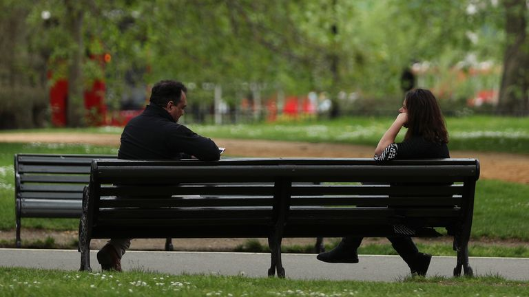 People observing social distancing on a bench in Hyde Park, London
