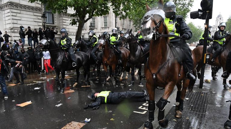 A mounted police officer lays on the road after being unseated from their horse, during a demonstration on Whitehall, near the entrance to Downing Street in central London on June 6, 2020, to show solidarity with the Black Lives Matter movement in the wake of the killing of George Floyd, an unarmed black man who died after a police officer knelt on his neck in Minneapolis. - The United States braced Friday for massive weekend protests against racism and police brutality, as outrage soared over t