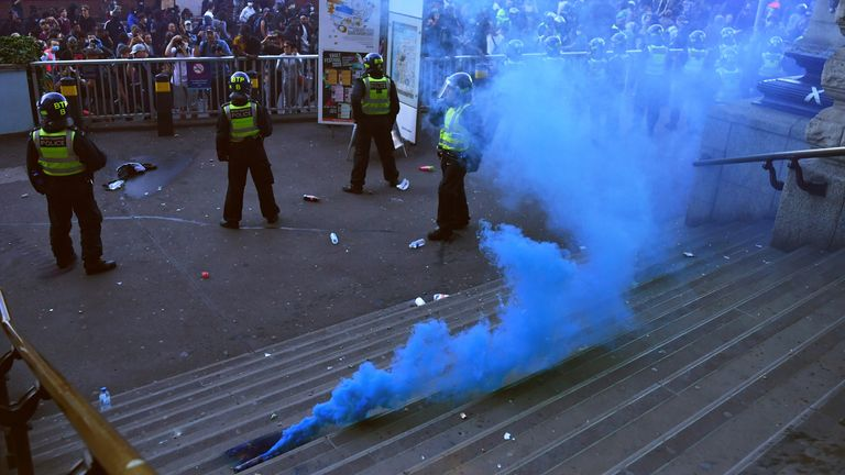 Police officers guard the Waterloo station, as the flare lies on the floor, during a Black Lives Matter protest in London