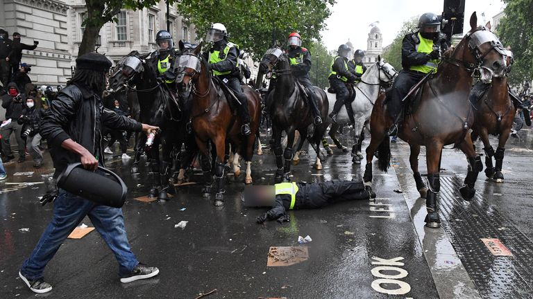 "A demonstrator points towards a mounted police officer laying in the road after being unseated from their horse, during a demonstration on Whitehall, near the entrance to Downing Street in central London on June 6, 2020, to show solidarity with the Black Lives Matter movement in the wake of the killing of George Floyd, an unarmed black man who died after a police officer knelt on his neck in Minneapolis. - The United States braced Friday for massive weekend protests against racism and police brutality, as outrage soared over the latest law enforcement abuses against demonstrators that were caught on camera. With protests over last week's police killing of George Floyd, an unarmed black man, surging into a second weekend, President Donald Trump sparked fresh controversy by saying it was a ""great day"" for Floyd. (Photo by DANIEL LEAL-OLIVAS / AFP) (Photo by DANIEL LEAL-OLIVAS/AFP via Getty Images)"