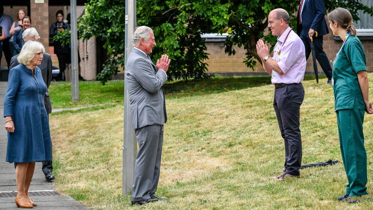 PABest..The Prince of Wales remains socially distanced as he a performs a namaste to Professor Mark Pietroni as he arrives with the Duchess of Cornwall at Gloucestershire Royal Hospital to meet front line key workers who who have responded to the COVID-19 pandemic during a visit to Gloucestershire Royal Hospital. PA Photo. Picture date: Tuesday June 16, 2020. See PA story ROYAL Charles. Photo credit should read: Ben Birchall/PA Wire
