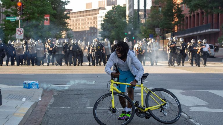 A protestor grabs his bike as the police uses tear gas and rubber bullets to disperse the crowd gathered near the White House on June 1, 2020 as demonstrations against George Floyd's death continue. - Police fired tear gas outside the White House late Sunday as anti-racism protestors again took to the streets to voice fury at police brutality, and major US cities were put under curfew to suppress rioting.With the Trump administration branding instigators of six nights of rioting as domestic terr