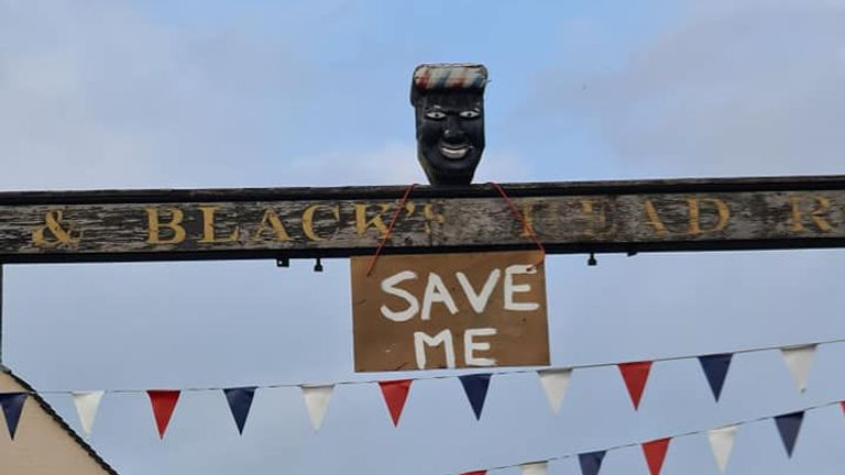 A sign saying 'Save Me' was seen hanging on a sign for the Greenman pub in Ashbourne, Derbyshire, before the head was removed