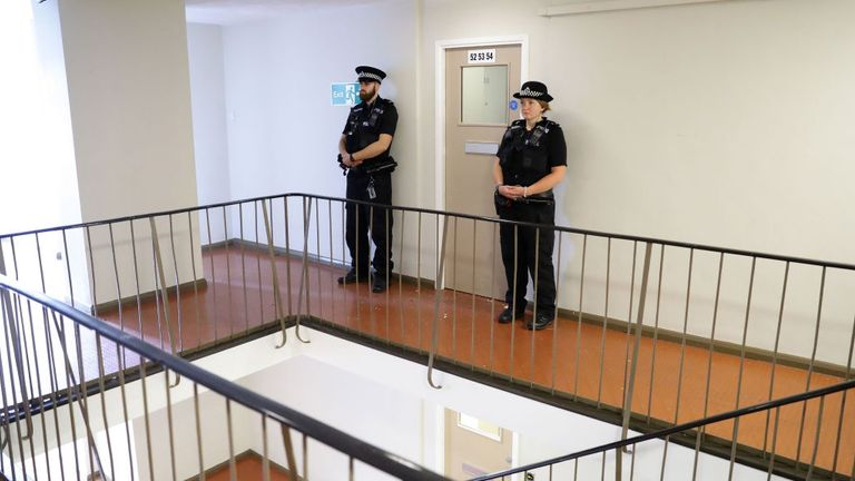 Officers stood guard outside the entrance to the corridor where Saadhalla's flat is believed to be
