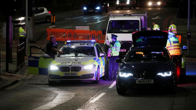 Police officers and their vehicles are seen at the scene of reported multiple stabbings in Reading, Britain, June 20, 2020. REUTERS/Peter Cziborra