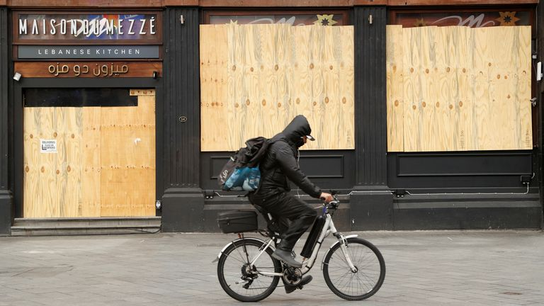 A cyclist passes a boarded up restaurant in Leicester Square