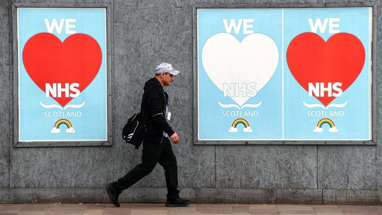 A man walks past posters paying tribute to NHS staff who continue to work to help patients during the coronavirus COVID-19 outbreak in Glasgow