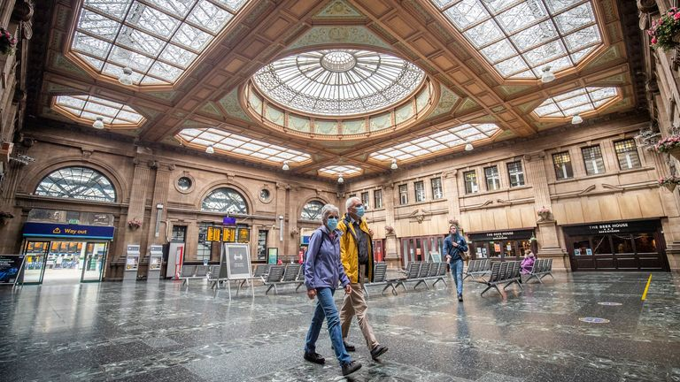 Two people wear face masks inside Waverley Station, Edinburgh