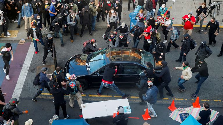 Protesters surround the car