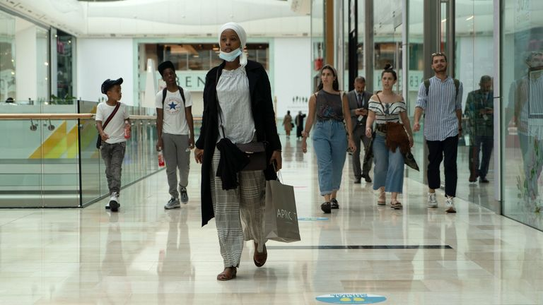 Customers, some wearing face masks or coverings as a precaution against COVID-19, walk past re-opened shops inside the Westfield indoor shopping centre in west Shepherds Bush, west of London on June 15, 2020 as some non-essential retailers reopen from their coronavirus shutdown. - Various stores and outdoor attractions in England are set to open Monday for the first time in nearly three months, as the government continues to ease its coronavirus lockdown. (Photo by Niklas HALLE'N / AFP) (Photo b