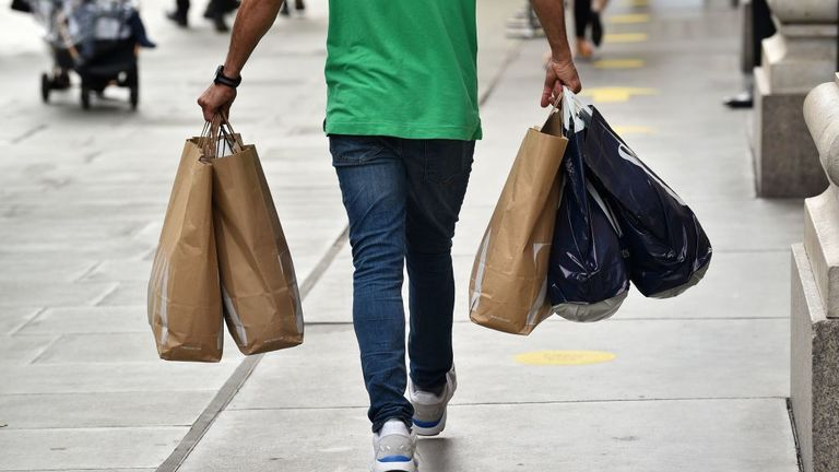 A shopper carries a variety of full shopping bags on Oxford Street in London