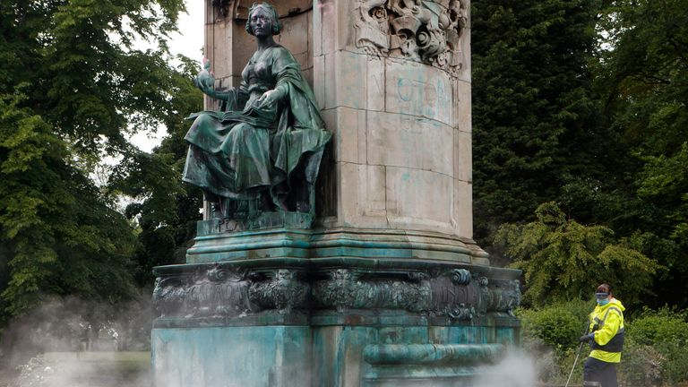 Council workers clean graffiti from a statue of Queen Victoria in Woodhouse Moor, Leeds