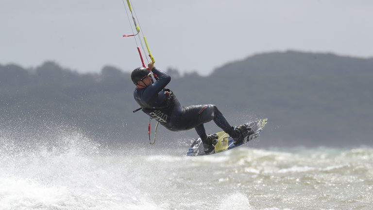 A kite surfer gets some air in the strong winds in the sea off of Lepe country park in Hampshire