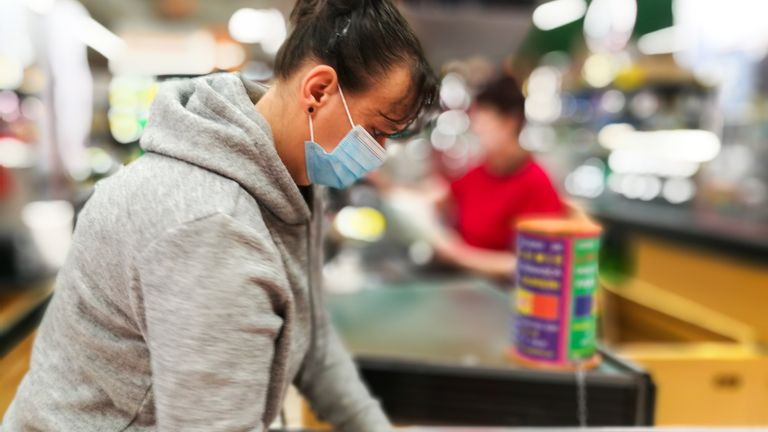 Woman wearing protective face mask and gloves at checkout