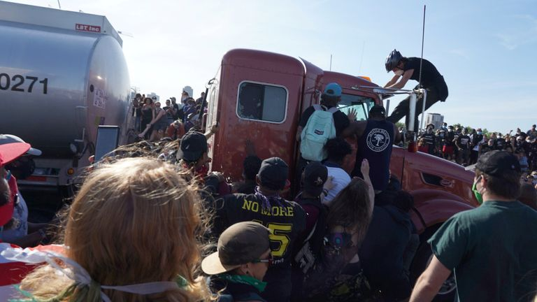 Protesters scale a truck that was driven into a rally in Minneapolis