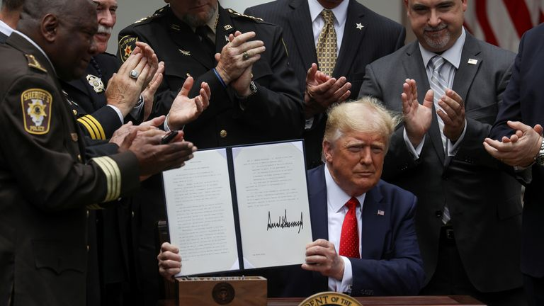 President Donald Trump displays an executive order on police reform during a signing ceremony in the Rose Garden at the White House in Washington, U.S., June 16, 2020.
