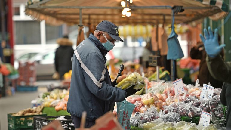 A shopper wears a facemask as he chooses produce at an open air market in Huddersfield,.West Yorkshire on June 4, 2020, as lockdown measures are eased during the novel coronavirus COVID-19 pandemic. (Photo by Oli SCARFF / AFP) (Photo by OLI SCARFF/AFP via Getty Images)