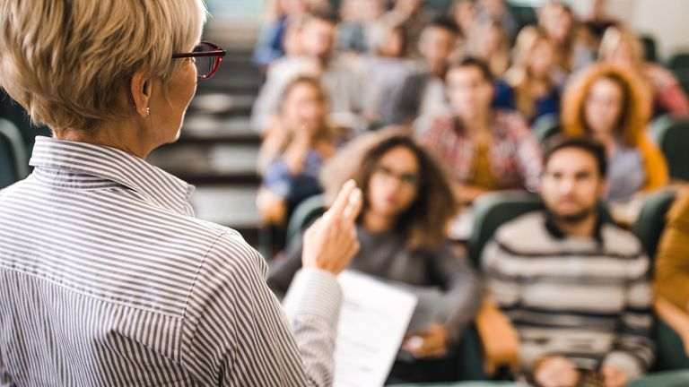 A tutor talks to a large group of students.in a university lecture theatre