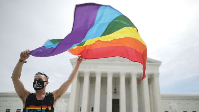 Joseph Fons holds a Pride flag outside the Supreme Court in celebration of the ruling