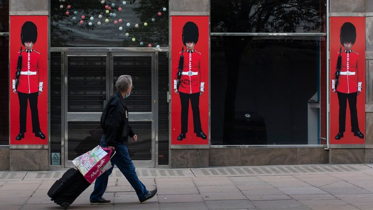 A man walks past a souvenir store on Oxford Street as shops and businesses remain closed on May 01, 2020 in London, England