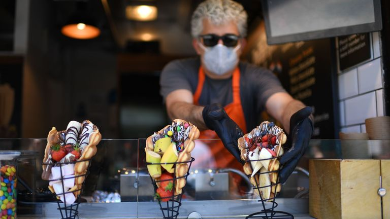 A vendor prepares waffles on his stall at Camden Market in London on June 1, 2020 as outdoor markets reopen following an easing of the lockdown restrictions during the novel coronavirus COVID-19 pandemic
