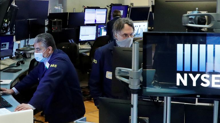 FILE PHOTO: Traders wear masks as they work on the floor of the New York Stock Exchange as the outbreak of the coronavirus disease (COVID19) continues in the Manhattan borough of New York, U.S., May 27, 2020