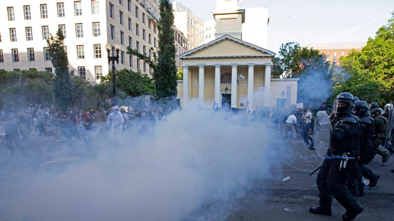 Police officers back demonstrators shooting tear gas next to St John's Church