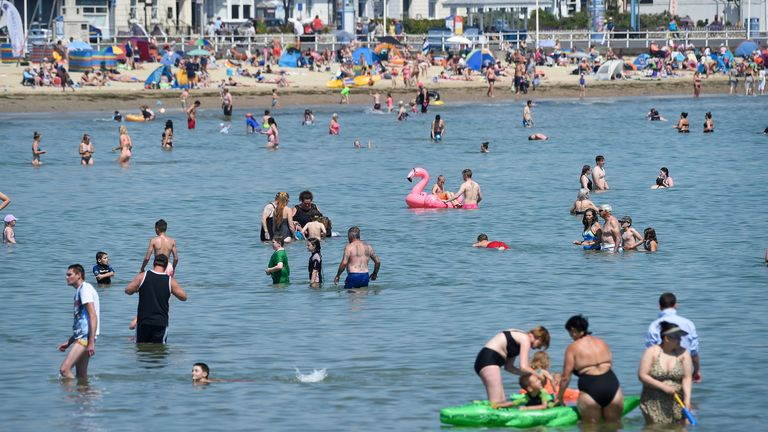 People swimming in the sea in Weymouth as UK temperatures soar