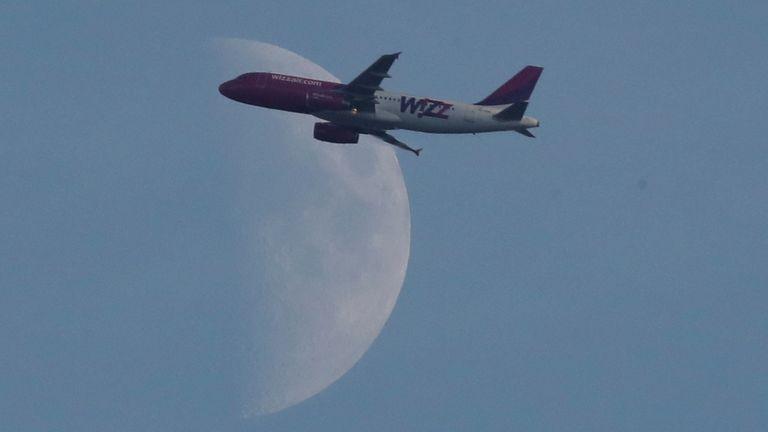 A Wizz Air passenger airplane flies past a Waxing Crescent moon, Harpenden, Britain, September 16, 2018. REUTERS/Peter Cziborra