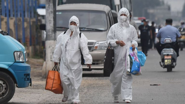 Two women wear protective suits as they walk on a street near the closed Xinfadi market in Beijing