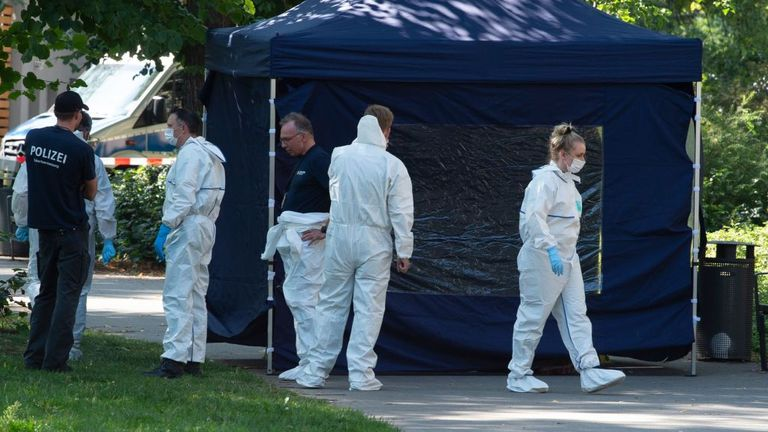 Forensic officers are seen combing the area for clues after the shooting in August last year