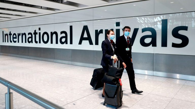 British Airways flight crew wear face masks as they arrive at Terminal 5 at London Heathrow