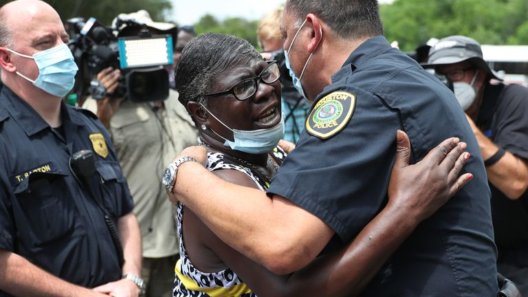 A woman hugs a police officer outside the church in Houston, Texas