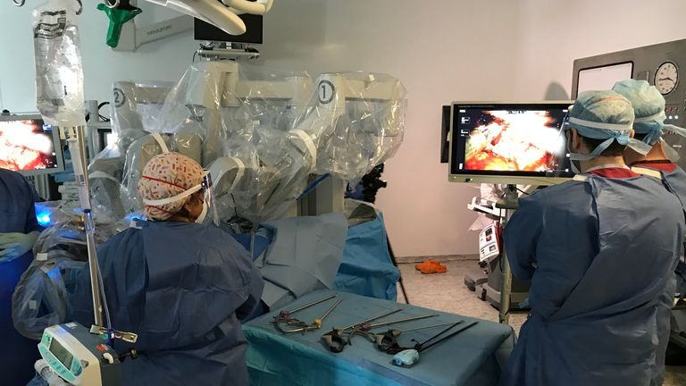 Surgeons wear full PPE to control a robot designed to remove a patient's prostate cancer