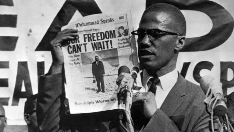 Malcolm X holds up a newspaper during a rally in New York City in 1963