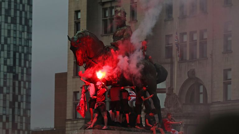 Liverpool fans let off flares on the statue of King Edward VII of Britain outside the Royal Liver Building in Liverpool. PA Photo. Picture date: Friday June 26, 2020. Fans are being urged to celebrate the club...s Premier League triumph at home as police believe more gatherings are planned after thousands filled the streets outside Anfield. See PA story SPORT Liverpool. Photo credit should read: Peter Byrne/PA Wire