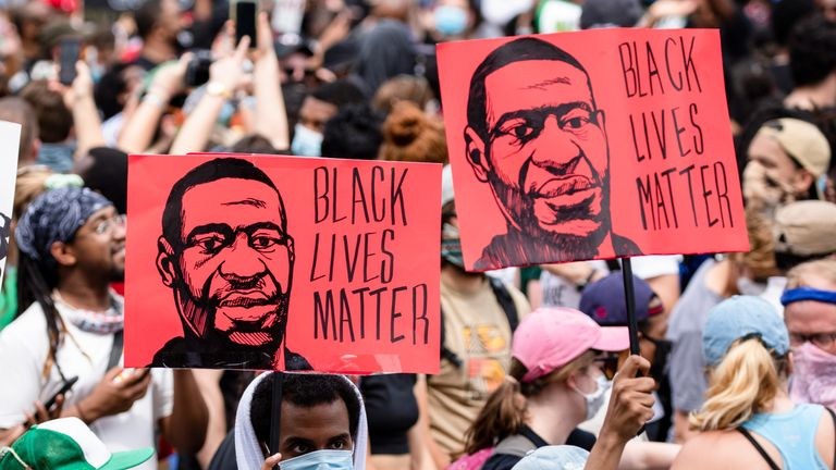 Protesters walk with signs near the White House during George Floyd protests on June 6, 2020 in Washington, DC