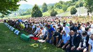 Bosnian Muslim men wearing face masks mark the 25th anniversary of the Srebrenica massacre