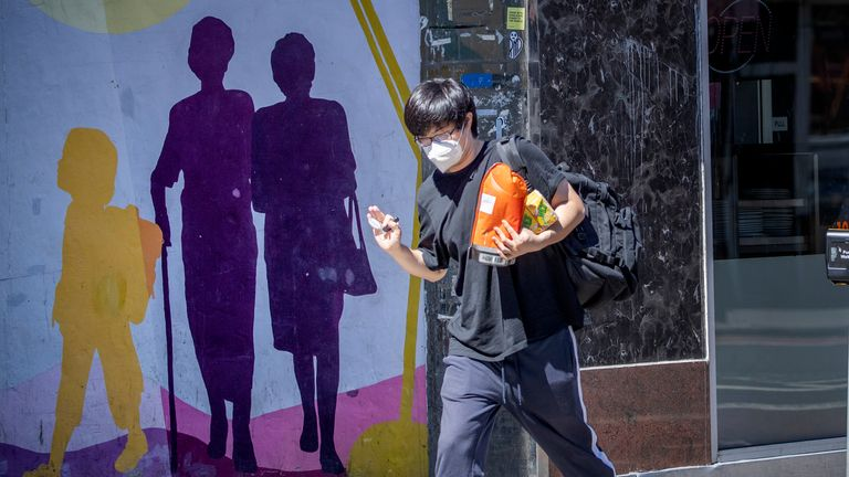 A man wearing a protective face mask carries his shopping in Edinburgh, as people can meet family and friends outdoors and play sports such as golf and tennis again as Scotland is moving into phase one of the Scottish Government's plan for gradually lifting lockdown.